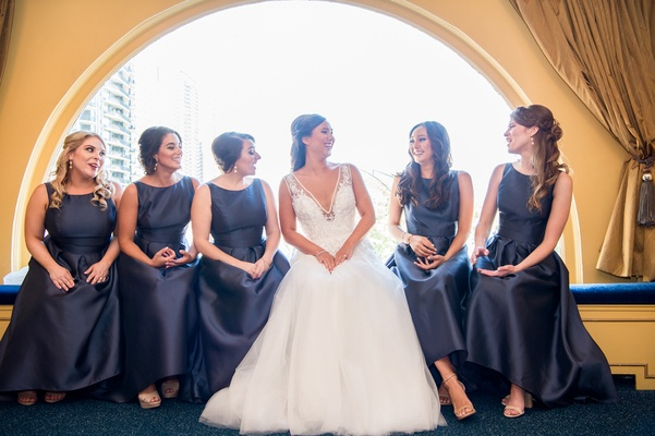 bride in hayley paige, bridesmaids in navy alfred sung high-low dresses with boat neckline