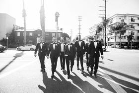 black and white photo of groom in lanvin tuxedo and groomsmen walking across the street