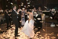 Bride in a Inbal Dror wedding gown with sparkly straps dances with Greek groom in black tuxedo