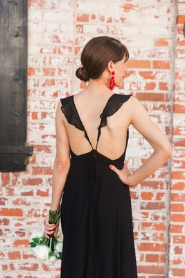 Black low back bridesmaid dress ruffle strap holding white flower bouquet red earrings