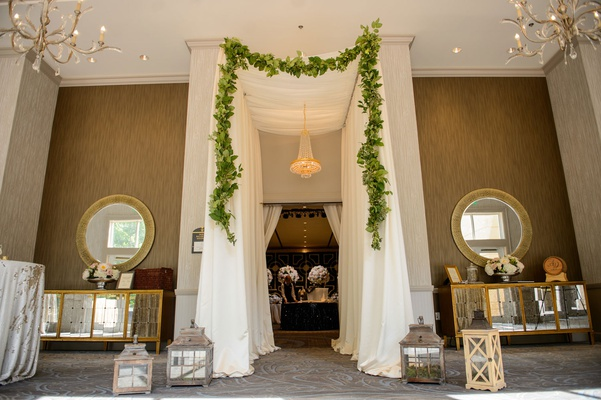Wedding reception entrance tall ceiling drapery garland chandelier two mirrors buffet sideboard