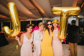wedding guests holding gold mylar balloons with bride and groom initials