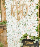Wedding reception photo guest book booth with flower wall made by bride monogram garden roses gold