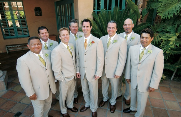 Groom with seven groomsmen in khaki suits and green ties