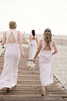 Bridesmaids with light pink bridesmaid dresses keyhole back walking on wood plank boardwalk sand