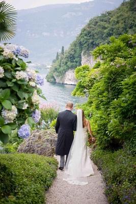 Bride and groom walking through gardens in Lake Como