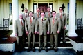 Groom and groomsmen in light brown suits with striped ties
