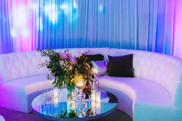 Wedding reception white lounge furniture mirror coffee table flower arrangement bright lighting