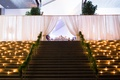 stairs up to couples wedding reception small candles greenery railing white fabrics