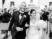 black and white photo of bride and groom smiling during recessional