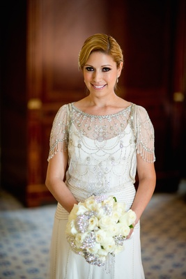 Bride in Jenny Packham dress with beading and embroidery holds bouquet of white roses with brooches