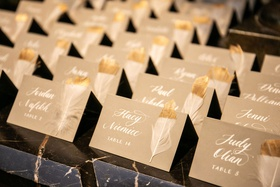 wedding reception escort card white calligraphy white feather dipped in gold paint on marble table