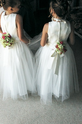 White flowing gowns tied with ribbon and flowers