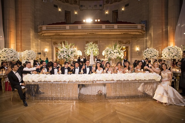 Bride and groom with bridesmaids and groomsmen at head table crystals flower runner ballroom chevron