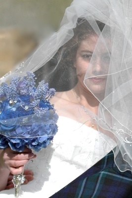 Bride with veil over face and blue bouquet