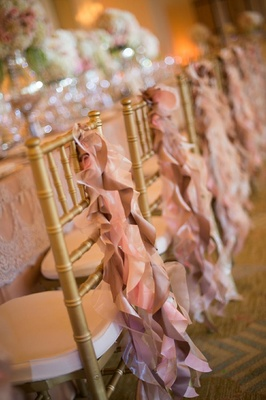 Pink ruffle ribbon fabric on back of gold reception chairs