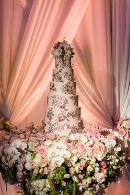 Wedding cake on table with white orchid pink roses drapery blush cake with gold detailing frosting