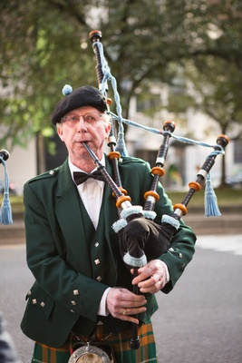Man in green jacket and kilt playing bagpipes