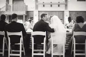 newlyweds sitting at table kiss