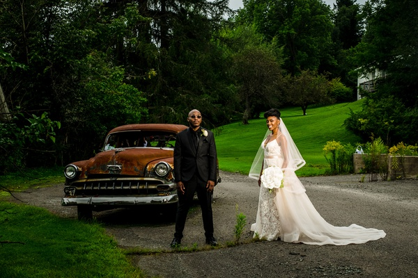 bride in eddy k lace wedding dress blush overskirt, groom in all black, edgy wedding portraits