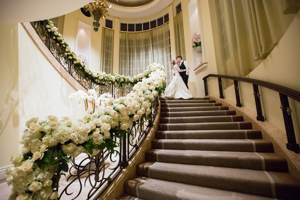 Bride and groom portrait on stairs to ballroom at beverly hills hotel white rose hydrangea greenery