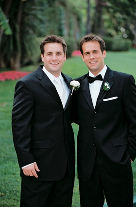 Best man wearing a black tuxedo with a white tie and rose boutonniere