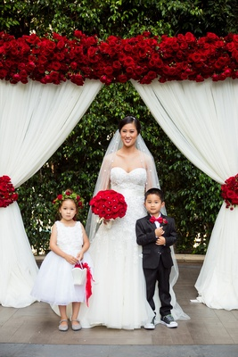 bride in liancarlo, flower girl with red rose flower crown, ring bearer in red bow tie