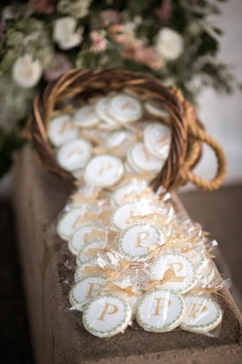 wedding favors in wicker basket wrapped cookie with laurel wreath design and initial monogram
