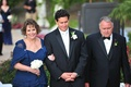 Parents in formal attire walking groom down aisle