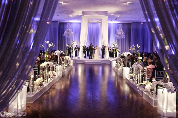 Purple wedding ceremony in ballroom with drapery