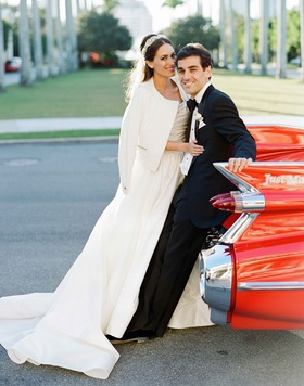 Bride in cool white jacket over wedding dress with groom in tuxedo at back of their classic red car
