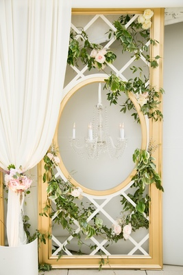 Gold door frame with chandelier & floral decor.
