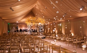 Tented wedding ceremony with hanging flowers