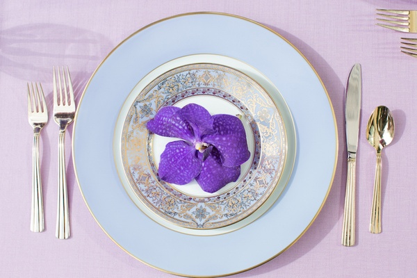 Wedding reception table setting with light blue rim, gold Versace china and golden flatware
