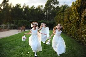 Three flower girls running in white dresses at wedding