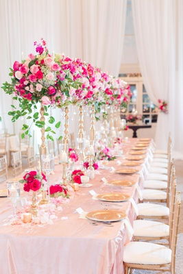 wedding reception long table pink linen gold chairs tall risers green leaves pink rose flowers