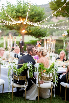 bride and groom sitting in gold chairs foliage ribbon kiss head table candelabra strung up lights