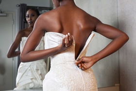 bride zipping back wedding dress