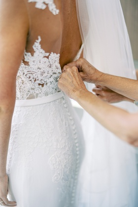 mother of bride helping daughter button wedding dress pronovias lace form fitting design illusion
