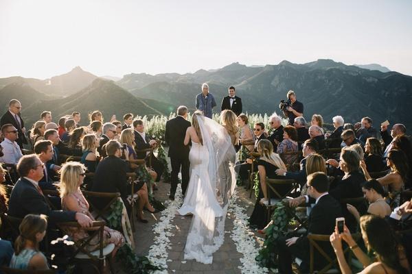 bride in strapless romona keveza wedding dress sweetheart neckline walks down aisle with parents