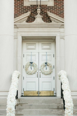 Perkins Chapel wedding decorations with white flower wreaths and blue ribbon