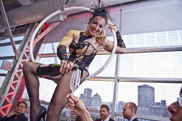 burlesque style acrobat on hoop pours guests champagne