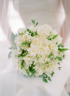 classic wedding bouquet with white flowers roses lily of the valley and greenery behind veil