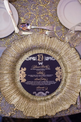 gold charger with round purple menu embossed with gold, purple linens with gold detailing