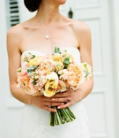 spring wedding ideas bright peach yellow pink orange wedding bouquet bride holding stems greenery