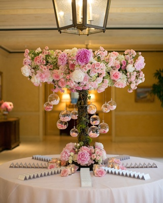 Escort card table with terrarium and pink peony rose decorations