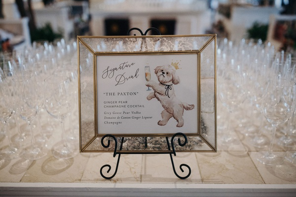 Signature drink menu in frame on stand drawing of dog holding drink cocktail champagne