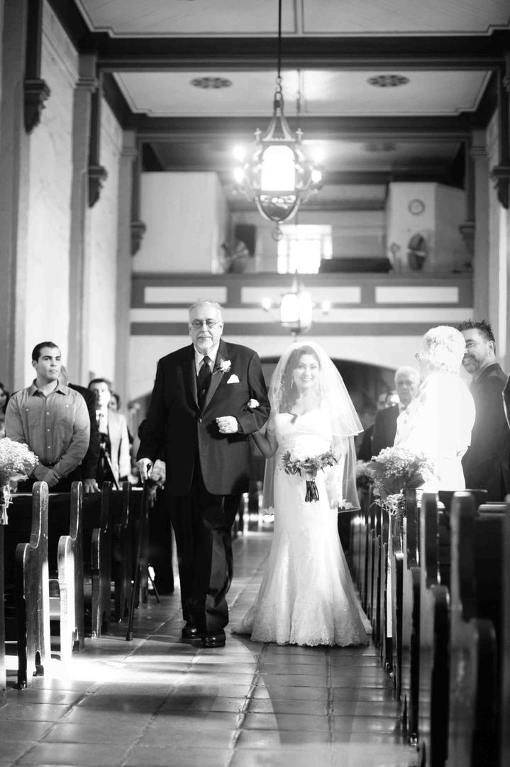 Black and white photo of man with cane escorting bride