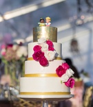 White wedding cake with gold top tier Fischer Price Little People cake topper fresh flowers pink whi