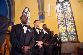 Groomsmen in tuxedos with bow ties at Chicago church wedding ceremony with Nigerian traditions